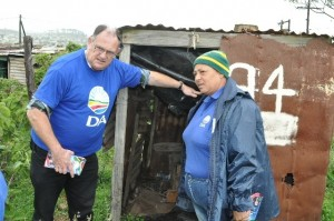MPL Dacre Haddon inspects a makeshift longdrop in the Zolani informal settlement with Grahamstown ward councillor Marcelle Booysen.